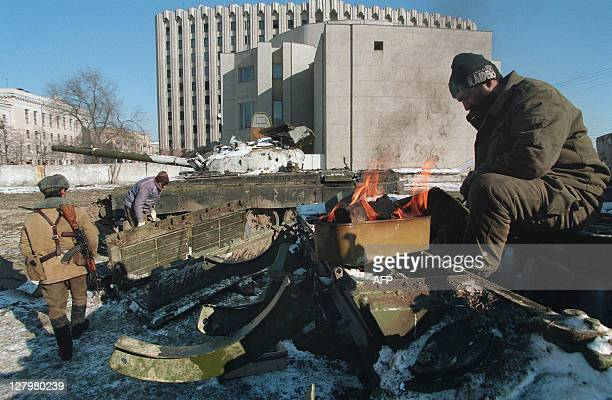 Russian army major Ivanov gets warmer as his comrade guarded by a Chechen soldier repairs a tank in the backyard of the presidential palace in Grozny...