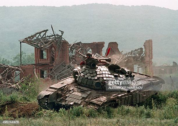 A Russian Army tank passes by a destroyed house in the Chechen stronghold of Bamut in May 1996 a village in western Chehnya during the battle between...