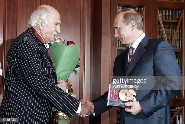 Russian army theatre actor Vladimir Zeldin shakes hands with Russian President Vladimir Putin after he was awarded with the State Order at the...