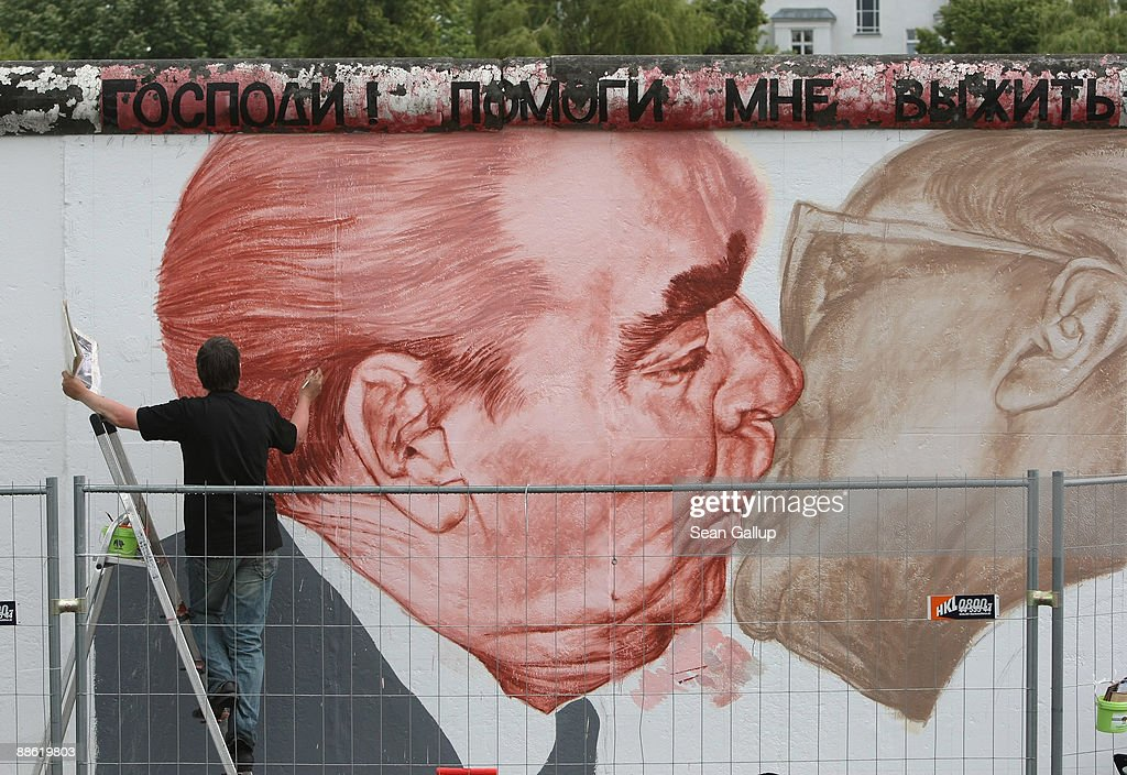 Russian artist Dmitry Vrubel repaints his historic mural showing former Soviet leader Leonid Brezhnev (L) kissing former communist East German leader Erich Honecker at a surviving portion of the Berlin Wall on June 22, 2009 in Berlin, Germany. The mural is on a portion of the Wall known as the East Side Gallery, and city authorities have invited artists to redo their works as part of a restoration effort. The Berlin Wall was built by the East German government and divided East and West Berlin from 1961 until 1989. Germany will mark 20 years since the fall of the Berlin Wall this year with an international commemoraiton in November.