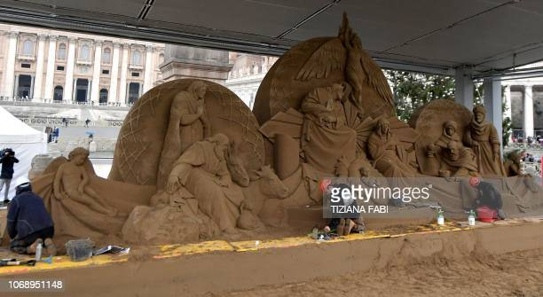 Russian artist Ilya Filimontsev and Czech artist Radovan Zivny sculpt sand to construct a nativity scene at Piazza San Pietro in The Vatican on...