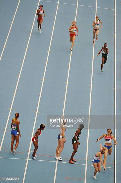Russian athlete Lyudmila Litvinova hands the baton to teammate Antonina Krivoshapka as they compete in the women's 4x400 metres relay heats at the...