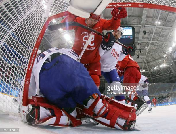 Russian athlete Sergei Shirokov collides with goalie Lars Haugen of Norway during the men's quarter-final ice hockey match between Norway and the...