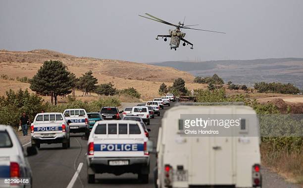 Russian attack helicopter hovers over a convoy of Georgian police and international journalists on August 14 2008 in the outskirts of Gori Georgia...