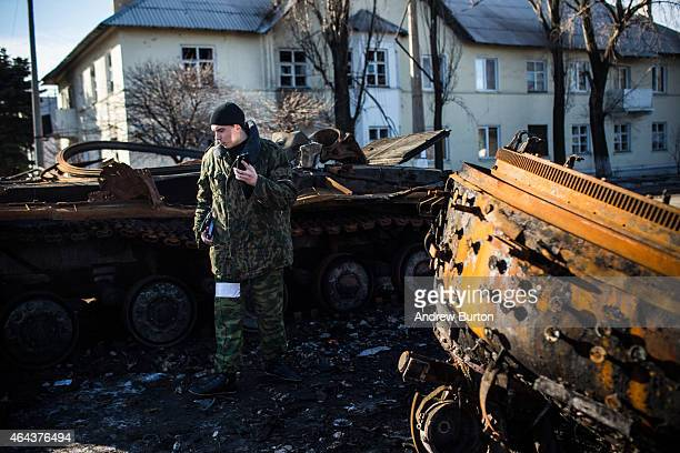 Russian backed rebel examines a destroyed tank on February 25 2015 in Enakievo Ukraine After approximately one month of fighting Russian backed...