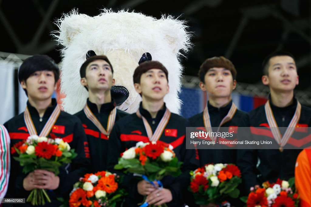 A Russian bear mascot stands behind the Chinese team as they receive their Gold medals for the Men's 5000m Relay on day three of the ISU World Short Track Speed Skating Championships at the Krylatskoe Speed Skating Centre on March 15, 2015 in Moscow, Russia.