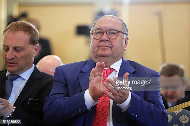 Russian billionaire Alisher Usmanov right applauds during panel sessions at the annual meeting of the Russian Union of Industrialists and...