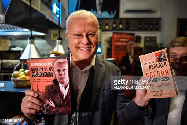 Russian billionaire businessman Alexander Lebedev holds the English and Russian editions of his autobiographical book in front of the media at a...