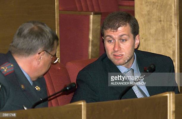 Russian businessman Roman Abramovich talks with a police officer during a Duma session in Moscow 17July 2000 Abramovich purchased 5009 per cent of...