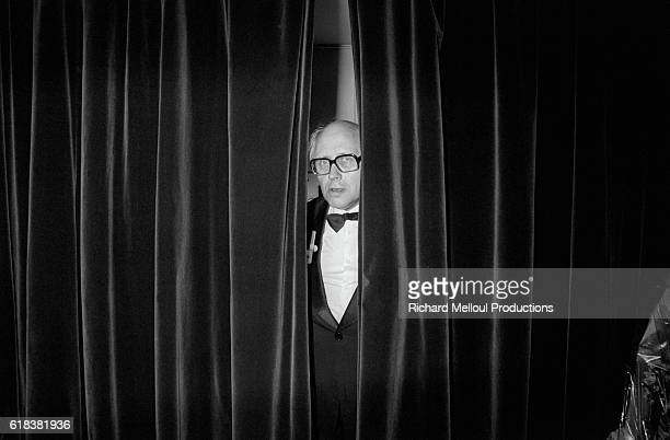 Russian cellist Mstislav Rostropovich looks out from behind the theater curtains before a rare concert in Paris