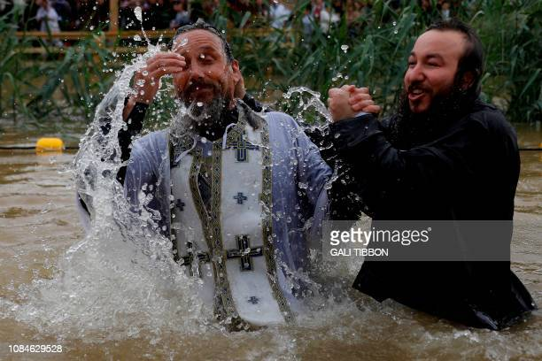 Russian Christian Orthodox priest baptises a pilgrim in the muddy waters of the Jordan River on January 18 2019 during the Epiphany celebrations at...