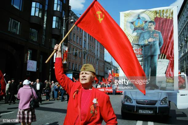 Russian communist holds a red flag near a placard depicting former Soviet leader Josef Stalin as he participates in the annual military parade at Red...