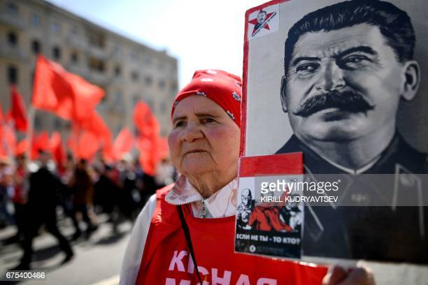 A Russian Communist party activist carries a banner with a portrait of late Soviet leader Joseph Stalin during a May Day rally in central Moscow on...