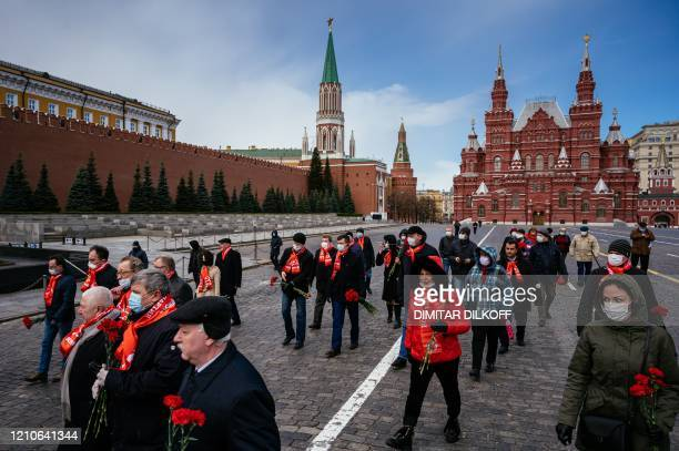 Russian Communist party members and supporters walk towards the Mausoleum of the Soviet state founder and revolutionary leader Vladimir Ilyich...