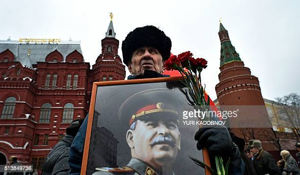 A Russian communist party supporter holds red carnations and a portrait of late Soviet leader Joseph Stalin near his tomb during a memorial ceremony...