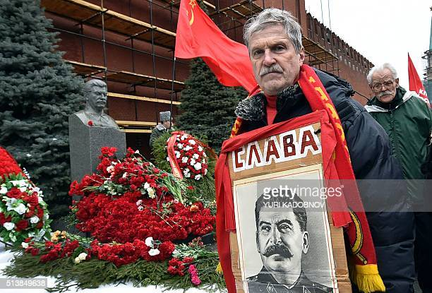 A Russian communist party supporter poses with a portrait of late Soviet leader Joseph Stalin near his tomb during a memorial ceremony to mark the...