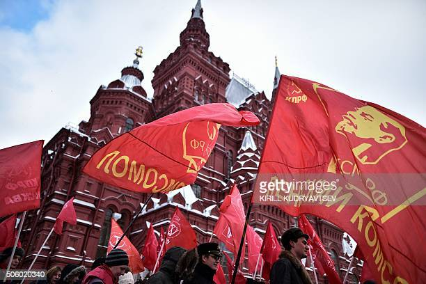 Russian Communist Party supporters carry red flags as they take part in a memorial ceremony to mark the 92st anniversary of late Soviet leader...