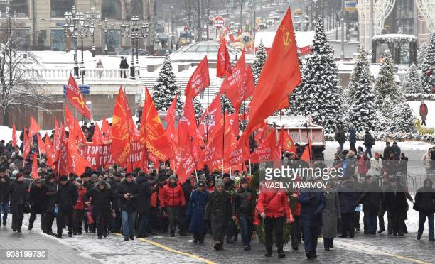 TOPSHOT Russian Communist Party supporters carry red flags as they take part in a memorial ceremony to mark the 94th anniversary of the death of...