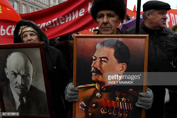 Russian communist supporters carry portraits of Soviet Union founder Vladimir Lenin and Soviet leader Joseph Stalin as they take part in a...