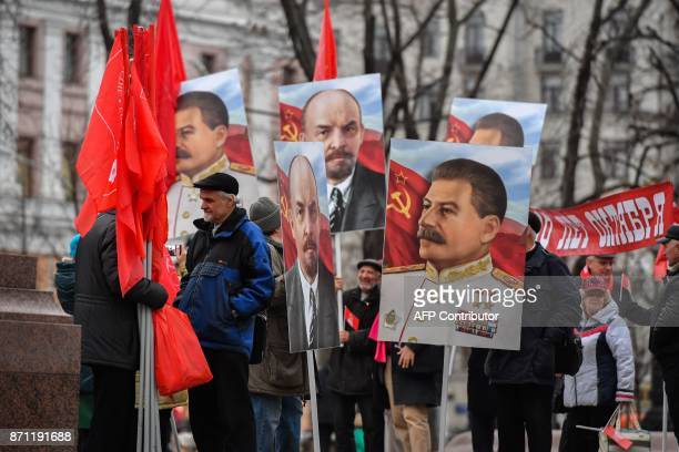 Russian Communist supporters holding posters depicting Soviet leaders Vladimir Lenin and Joseph Stalin gather for a rally marking the 100th...