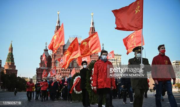 Russian Communist supporters march towards the Mausoleum of Vladimir Lenin to lay flowers on the 102nd anniversary of the Komsomol on Red Square in...