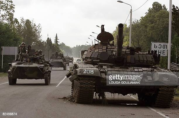 A Russian convoy drives past a destroyed tank in the village of Kheta while heading towards the border of Georgia and the Abhazian separatist...