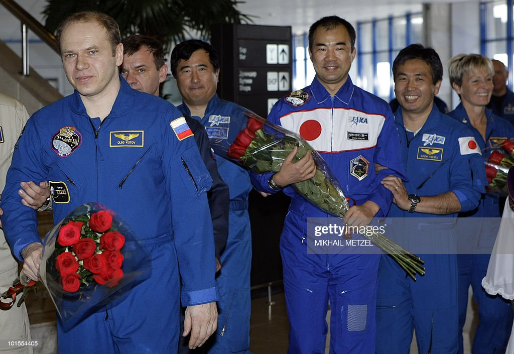 Russian cosmonaut Oleg Kotov (L) and Japanese Aerospace Exploration Agency astronaut Soichi Noguchi (C) get help as they walk to a press-conference at Karaganda airport in Kazakhstan on June 2, 2010. The Soyuz capsule, which carried the three astronauts safely returned to Earth after a half-year stint on the international space station, with a landing in the Kazakh steppe.