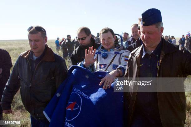 Russian cosmonaut Roman Romanenko waves as Russian space agency Roskosmos ground personnel carry him shortly after the landing aboard the Russian...
