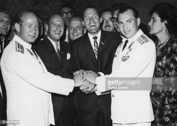 Russian cosmonauts and American astronauts join hands at a hotel in Athens Greece September 1965 From left to right Alexey Leonov Charles Conrad Jr...