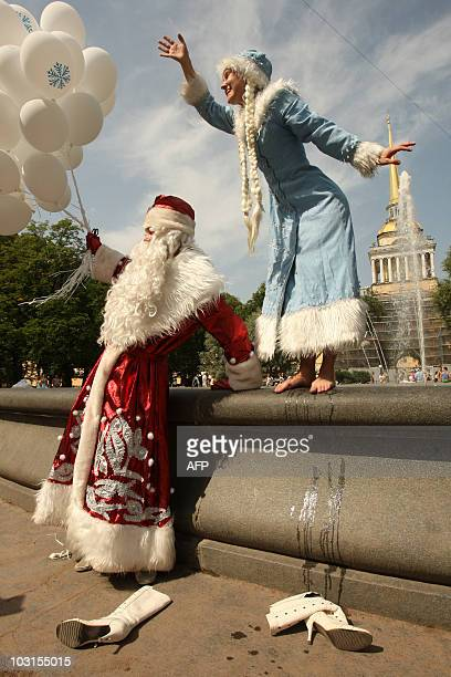 A Russian couple dressed as Father Frost and a snow princess dance near a fountain in central Saint Petersburg on July 28 2010 to take people's minds...