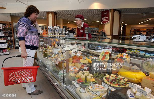 A Russian customer buys cheese in Saint Petersburg on August 7 2014 Russia retaliated against tough new Western sanctions banning most food imports...