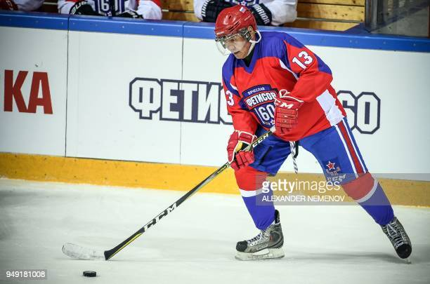 Russian Defence Minister Sergei Shoigu controls the puck during a hockey game devoted to the 60th anniversary of a famous Soviet and National Hockey...