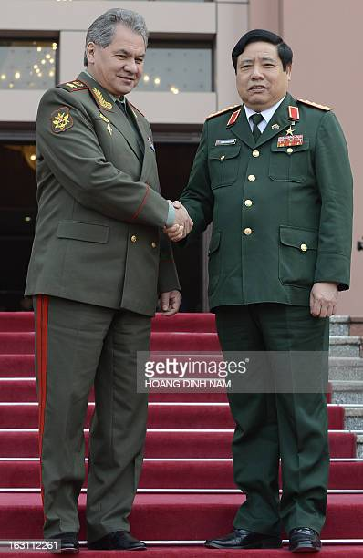 Russian Defense Minister Sergei Shoigu shakes hands with his Vietnamese counterpart Phung Quang Thanh as he leaves the Ministry of Defense's...