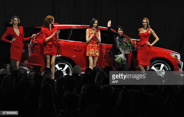"""Russian designer Valentin Yudashkin waves to fans after his show in Moscow on March 20, 2010 at the opening of """"Fashion Week in Moscow"""". AFP PHOTO/..."""