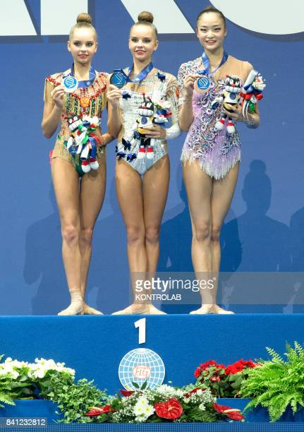 Russian Dina Averina Russian Arina Averina and Japanese Kaho Minagawa pose on the podium of the Hoop prizegiving ceremony during the FIG 35th Rhytmic...