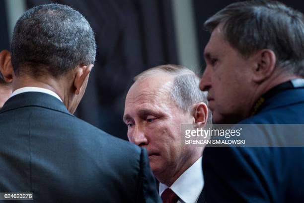Russian diplomat Yuri Ushakov listens while US President Barack Obama and Russia's President Vladimir Putin talk before an economic leaders meeting...