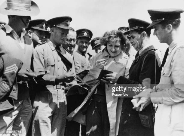 Russian discus thrower Nina Ponomaryova signing autographs for members of the Royal Australian Air Force, who surround Ponomaryova in the Olympic...