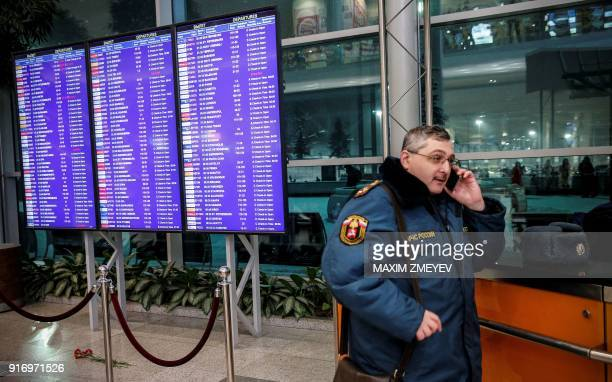 A Russian emergency employee stands next to flowers displayed in tribute to a plane crash victims under of the flight schedule timetables at the...