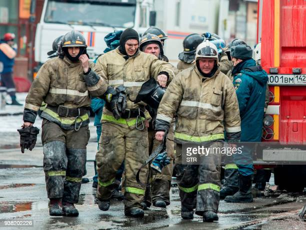 Russian emergency firefighters walk near a multistory shopping center in Kemerovo on March 26 2018 At least 53 bodies have been recovered from a fire...