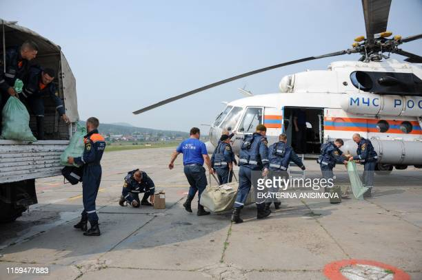 Russian emergency ministry officers load equipment into a helicopter as they prepare for departure to battle forest fires at an airfield in the...