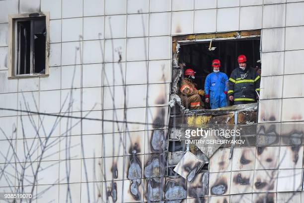 TOPSHOT Russian emergency service staff work at the site of a fire at a multistorey shopping centre in Kemerovo on March 27 2018 Russian authorities...
