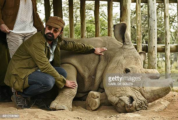 Russian entrepreneur and patron of the Giants Club Evgeny Lebedev poses next to the last male northern white rhino sudan at Ol Pejeta Sanctuary...