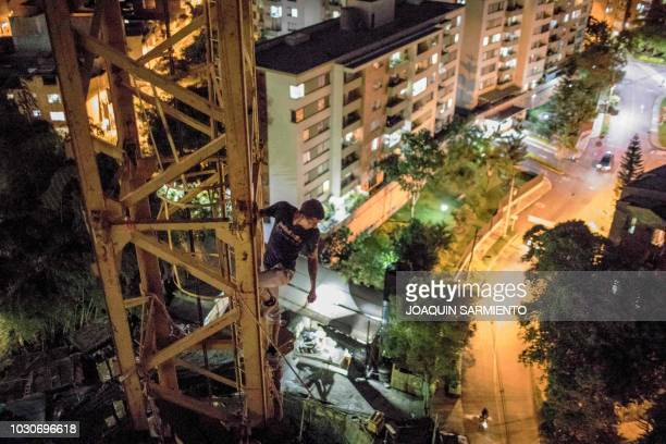 Russian extreme athlete Pavel Gogulan aka the Russian Spiderman climbs a crane next to a building under construction as a way to prepare to an...
