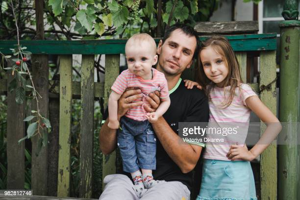 russian family. father with daughter and baby son on a bench near the house. - eastern european descent stock pictures, royalty-free photos & images