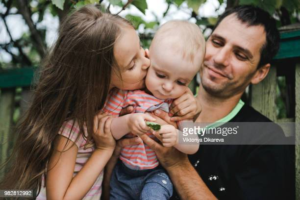 Russian family. Father with daughter and baby son on a bench near the house.