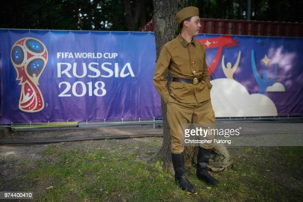 Russian fan dressed in 1969 period military uniform watches the big screen at the official FIFA Fan Fest at Moscow State University showing the first...