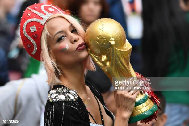 Russian fan kisses a replica of the FIFA 2018 World Cup trophy before the Russia 2018 World Cup Group A football match between Russia and Saudi...