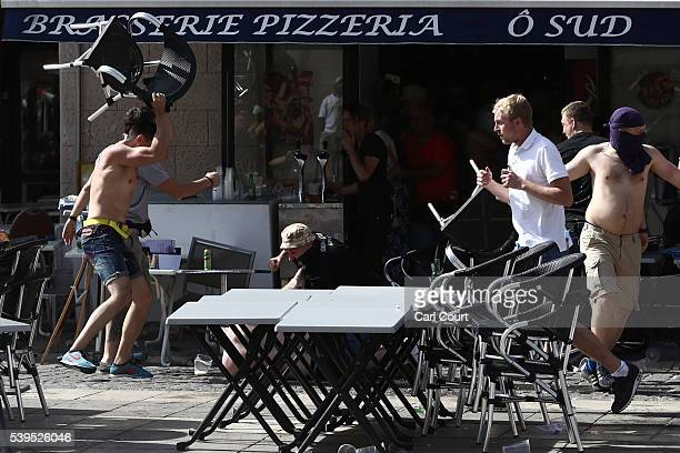 Russian fan smashes a chair over an England supporter as another attacks him on the ground as they clash ahead of the game against Russia later today...
