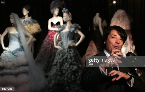 Russian fashion designer Valentin Yudashkin speaks near his creations during an exhibition in the State historical museum at Red Square in Moscow on...