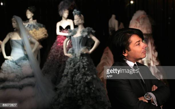 Russian fashion designer Valentin Yudashkin stands near his creations during an exhibition in the State historical museum at Red Square in Moscow on...
